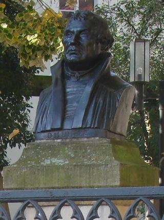 Bild: Die gusseiserne Kopie des Kopfes vom Wittenberger Lutherdenkmal steht vor dem Geburtshaus des Reformators in Eisleben.