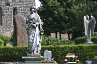Bild: Pieta auf dem Wipertifriedhof zu Quedlinburg. Im Hintergrund ist die Wipertikirche zu sehen.