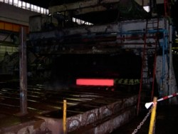 Bild: Das Breite Umkehr Walzwerk. Walzen von Kupfer-Nickel-Blechen. Das glühende Vormaterial passiert das Walzgerüst.