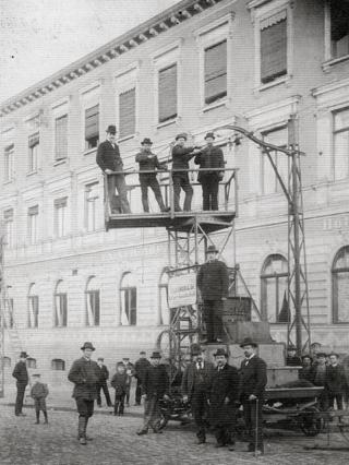 Bild: Bereits im Jahre 1899 wurden in Eisleben die ersten Vorbereitungen für den Betrieb der MANSFELDER ELEKTRISCHEN KLEINBAHN getroffen. Im Bild ist die Verlegung der Fahrleitungen durch das entsprechende Fachpersonal zu sehen. Dieses Bild ist gemeinfrei, weil seine urheberrechtliche Schutzfrist abgelaufen ist.