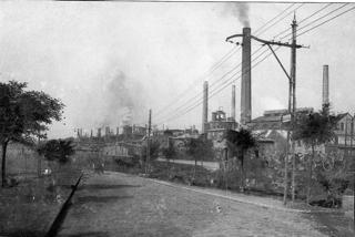 Bild: Blick auf die Krughütte (später: Karl-Liebknecht-Hütte) bei Eisleben. Im Bild sind noch die Schienen der Kleinbahn zu erkennen. Aufnahme aus der Zeit vor dem Ersten Weltkrieg. Dieses Bild ist gemeinfrei, weil seine urheberrechtliche Schutzfrist abgelaufen ist.