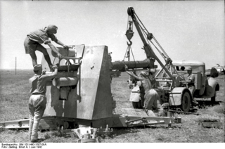 Bild: Wechsel eines Geschützrohres an der FlaK 88 in Nordafrika. Bild: Under the licence of Commons:Bundesarchiv. Bundesarchiv, Bild 101I-443-1587-09A / Zwilling, Ernst A. / CC-BY-SA.