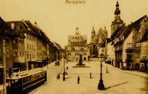 Bild: Die elektrische Kleinbahn auf dem Markt von Eisleben. Fotografie von Anfang des 20. Jahrhunderts. Dieses Bild ist gemeinfrei, weil seine urheberrechtliche Schutzfrist abgelaufen ist.