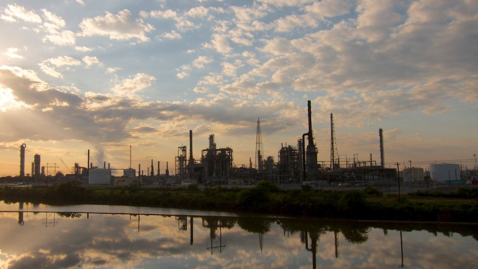 Texas City oil and gas refineries bellow steam at sunset.
