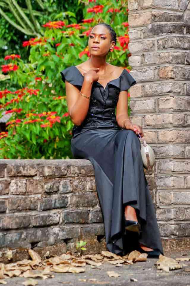 Nyasha sitting in a long black dress