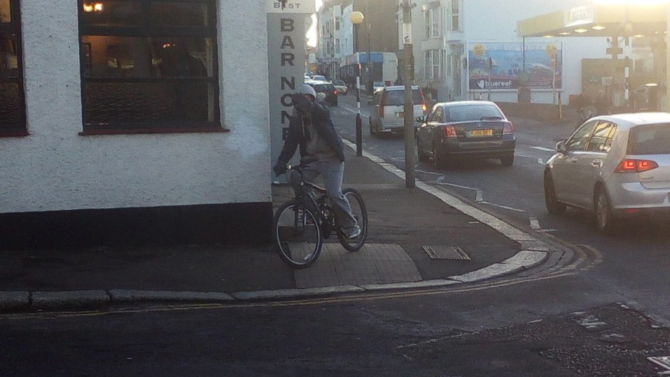 Pavement cyclist hiding face from being photoed.