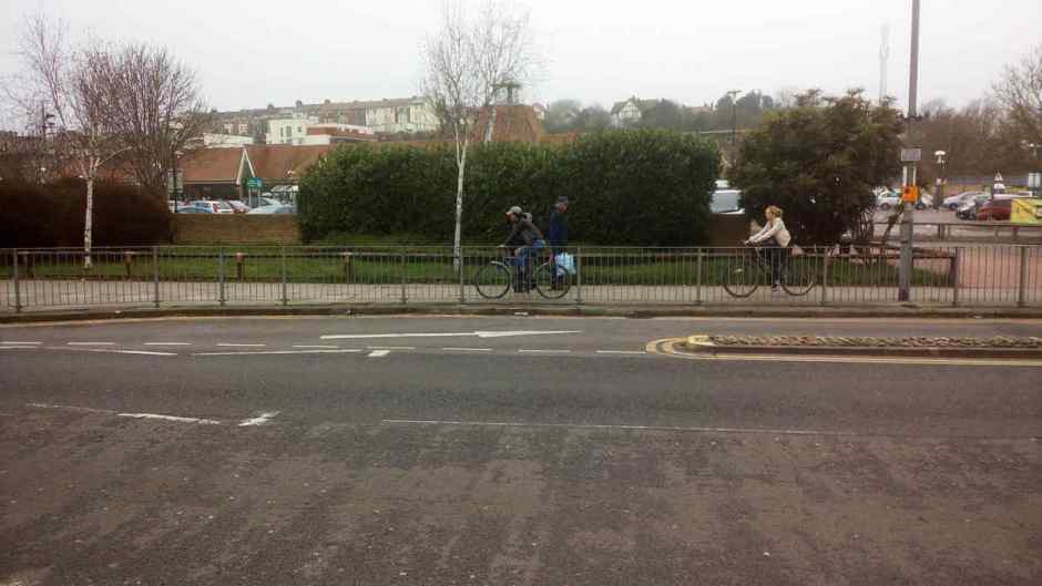 Two girls cycling on the pavement, Queens Road, Hastings