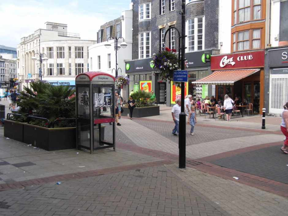 A no-cycling sign hidden by a flower basket and facing so no-one can see it. Wellington Place, Hastings.