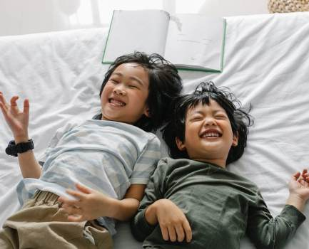 happy ethnic children lying on bed
