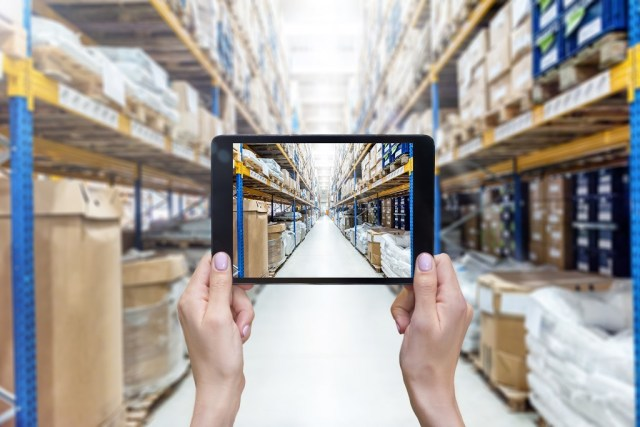 hands holding a digital tablet in a corridor of futuristic distribution warehouse. Large distribution storage in background with racks full of packages, boxes, pallets, crates ready to be delivered. Logistics, freight, shipping, receiving. Warehouse Management System from HaulTech