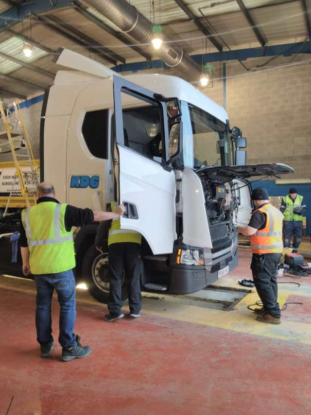 Engineers in high visibility jackets working on the Scania vehicle