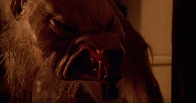 A still image taken from the horror film Ginger Snaps (2000). It shows the snarling, bloody face of a werewolf.
