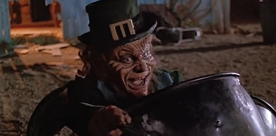 A still shot from the movie Leprechaun (1993), showing an evil-looking leprechaun smiling widely.