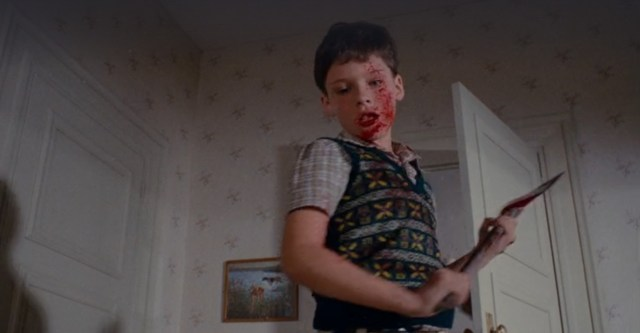 A still image taken from the Spanish/American horror film, Pieces (1982). It shows a young boy, splattered in blood and brandishing an axe.  Reviews in Retrospect: Pieces (1982).
