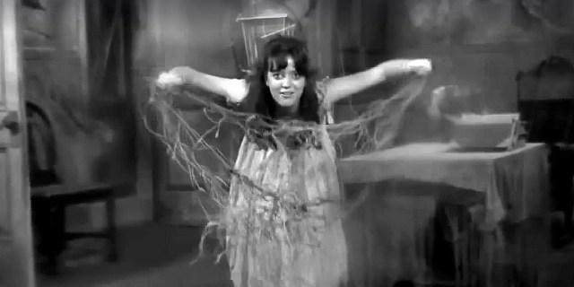 A screen shot taken from the 1968 horror film 'Spider Baby'. It shows a young woman with her arms spread out, holding knives and a net.  The Way Back Machine: Spider Baby (1968)