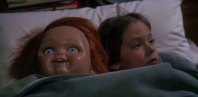 A screenshot taken from the 1988 horror film 'Child's Play'. It shows a young boy, laying in bed beside a plastic doll.  Top 5 Films Featuring Killer Dolls
