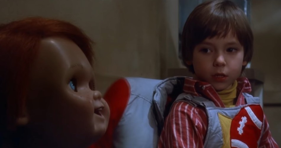 A screen shot taken from the 1988 horror film 'Child's Play'. It shows a young boy looking nervously at a doll. Top 5 Films Featuring Killer Dolls