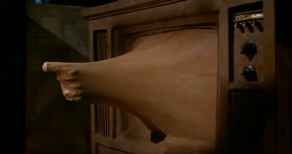 A screen shot taken from the 1983 film Videodrome. It shows a fleshy hand wielding a gun protruding from a TV set.