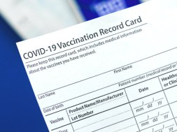 COVID-19 vaccination record card close up on table in hospital