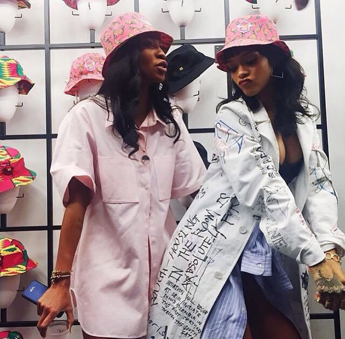 Rihanna wearing Melissa Forde for Wrkng Title M$$xWT pink pinepple print bucket hat, Raf Simons Fall 2015 white graffiti coat, Lynn Ban yellow gold and diamond coil ring, squre hoop earrings, circuit rings and Reverso ring and bracelet