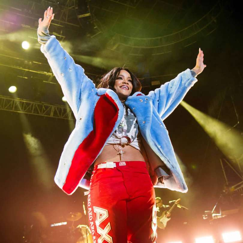 Rihanna at March Madness Music Festival wearing Kye Fall 2015 blue and red crystal-embellished fur jacket, vintage The Cramps t-shirt from Chapel NYC, AXO red motocross pants, Neil Lane cross necklace and diamond rings