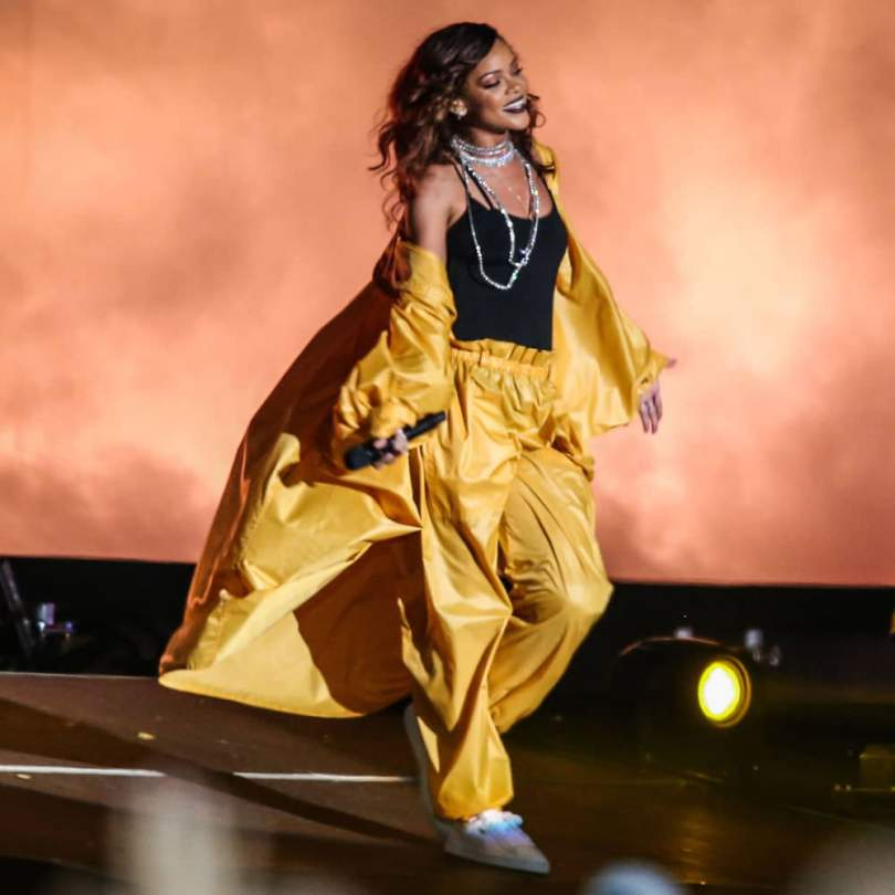 Rihanna wearing Issey Miyake vintage yellow windsuit, Puma Basket classic sneakers, Fallon Monarch pointed choker at Rock In Rio Brazil 2015
