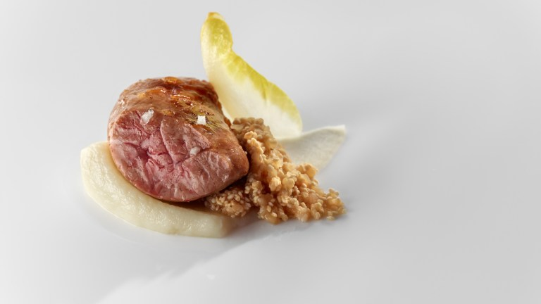 Castañuelas (pork salivary glands) in walnut confit with mashed rice germs and endive. Photo: José Luis López de Zubiria