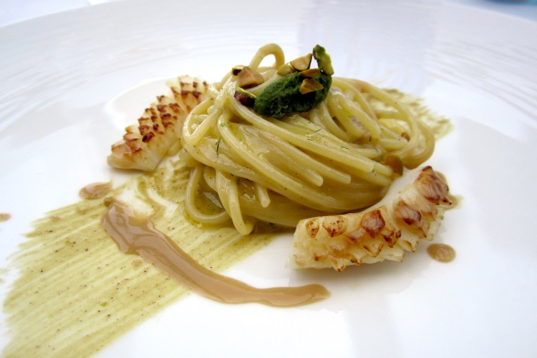 Spagnetti with colatura di alici (anchovy sauce), squid and pesto of his offal, pistachi and lemon