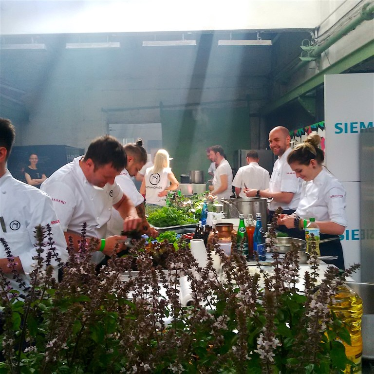 Chefs preparing their dishes for the final dinner in the premises of the old shipyard
