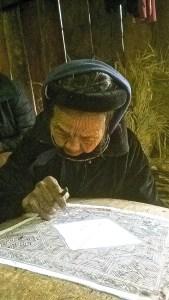93 year old woman batiking intricate Hmong design