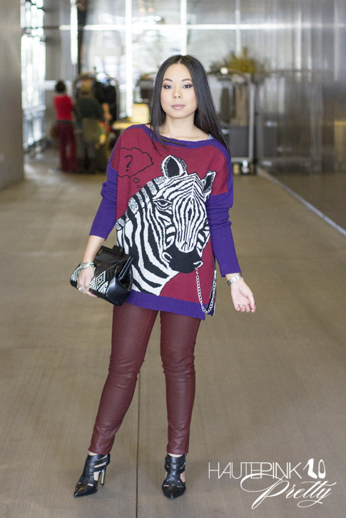 An Dyer wearing Ainsley Zebra TALA INTARSIA PULLOVER, Bleulab Ruby Coated Jeans, ShoeMint Garbo Pumps, Koret Woven Aztec Neo Framed Clutch
