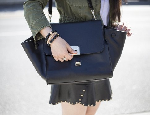 An Dyer wearing JewelMint Layered Ice Ring, Faux Leather Skirt with Gold Studs, Zara Army Anorack, BesoBeso by Luka Bracelets, Cuore & Pelle Caterina Trapeze Bag