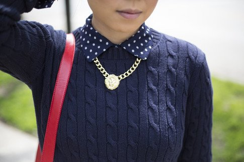 An Dyer wearing Sole Society Britt Messenger Bag in Red, Gold Lion Head Necklace, Navy Polka Dot Blouse, American Apparel Navy Cable Knit Sweater