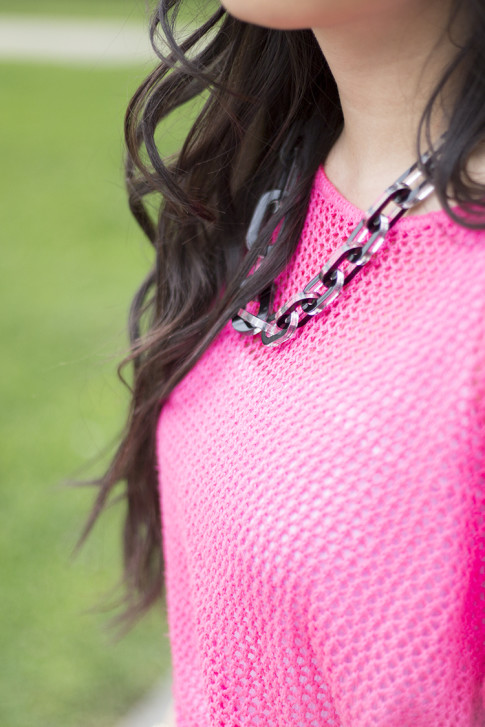 An Dyer wearing neon hot pink  fishnet sweater & jewelmint Shadow Link Necklace