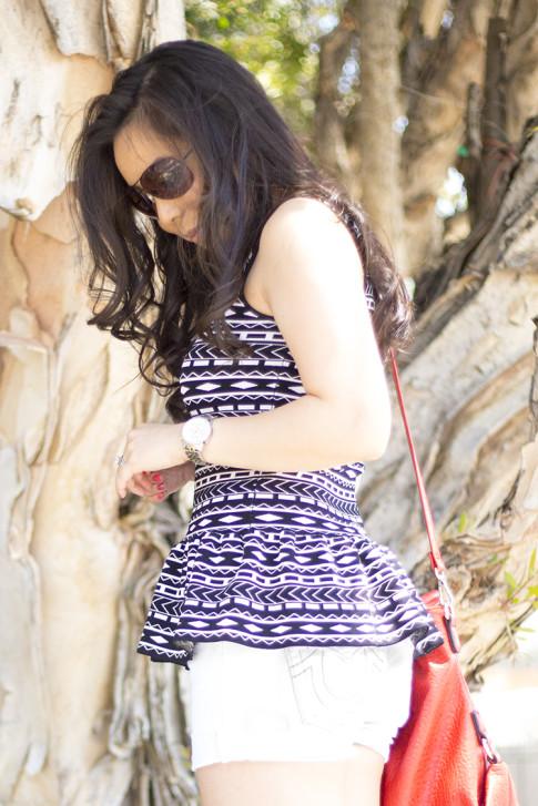 An Dyer wearing JewelMint Tribal Fringe Collar Necklace, Torn by Ronny Kobo Michaela Tribal Peplum Tank, True Religion White Shorts, Vaunt Snake Aviators