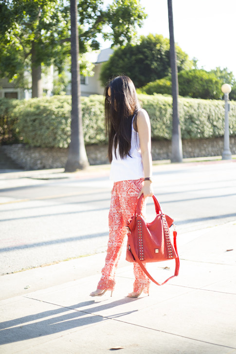 An Dyer wearing Michael Stars Sleeveless Scoop Neck Tank Dress, Chaser Brand Red Tribal Pants, V-Couture by Kooba Ruby Contour Studded Convertible Tote in Coral, Bebe Jacqueline Sandals
