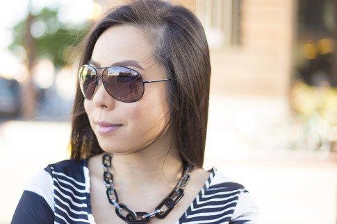 An Dyer wearing Vaunt Black Snake Print Etched Aviator Sunglasses, JewelMint Shadow Link Necklace, Vintage Havana Striped Top