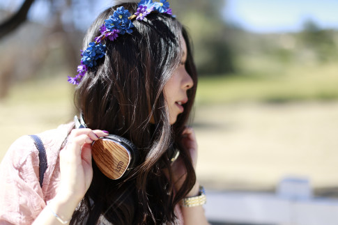 An Dyer wearing Purple Blue Flower Crown Coachella Festival Style LSTN Headphones Woodgrain