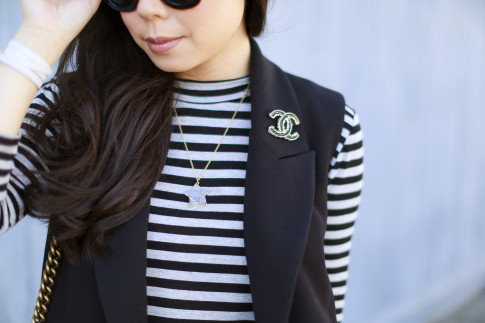 An Dyer wearing Wren Star Necklace with Chanel Brooch and vest sleeveless coat