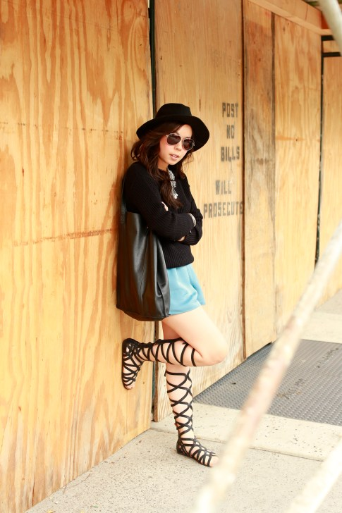 An Dyer wearing Kenneth Cole Gentlesouls Gladiator Sandals, Delikate Rayne Shorts with black fedora panama hat