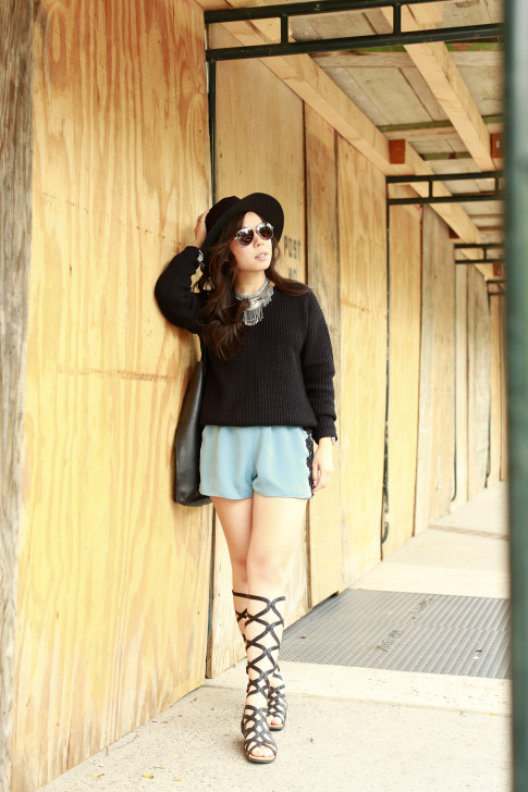 An Dyer wearing MADE eyewear Sunglasses, Gentlesouls Gladiator Sandals, Delikate Rayne Shorts with black fedora panama hat