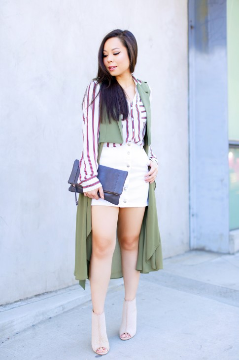 An Dyer wearing Drapey Sleeveless duster coat, button front white denim mini skirt