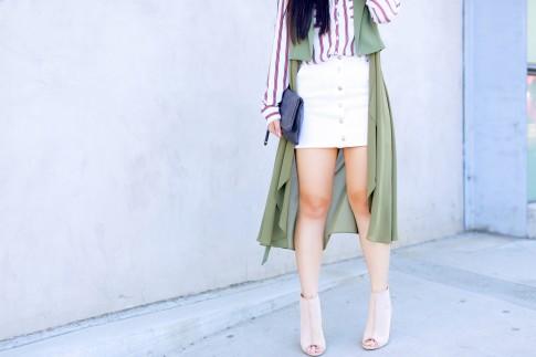 An Dyer wearing Drapey Sleeveless duster coat, button front white denim mini skirt