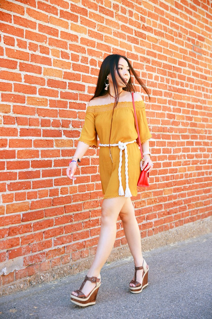An Dyer wearing mustard yellow off the shoulder dress, brown platforms