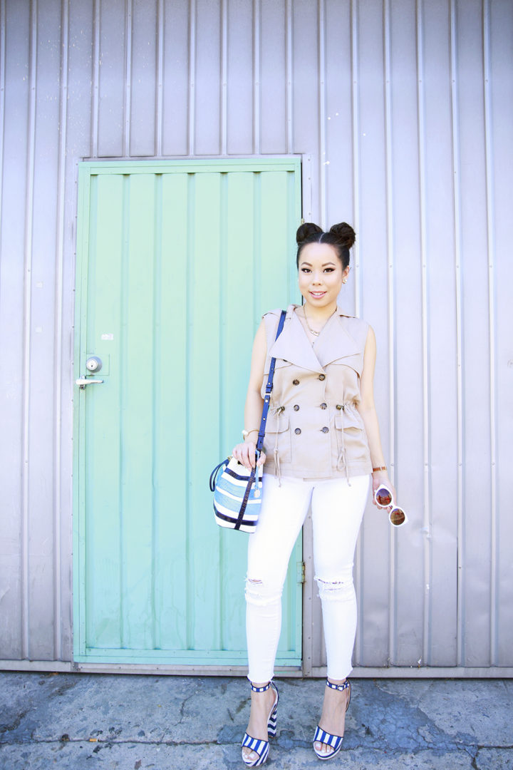 An Dyer wearing Charming Charlie Sunglasses ,Brahming Stripe Bucket Bag, Kut from the Kloth Trench Vest with White jeans and Navy Striped Platform Sandals