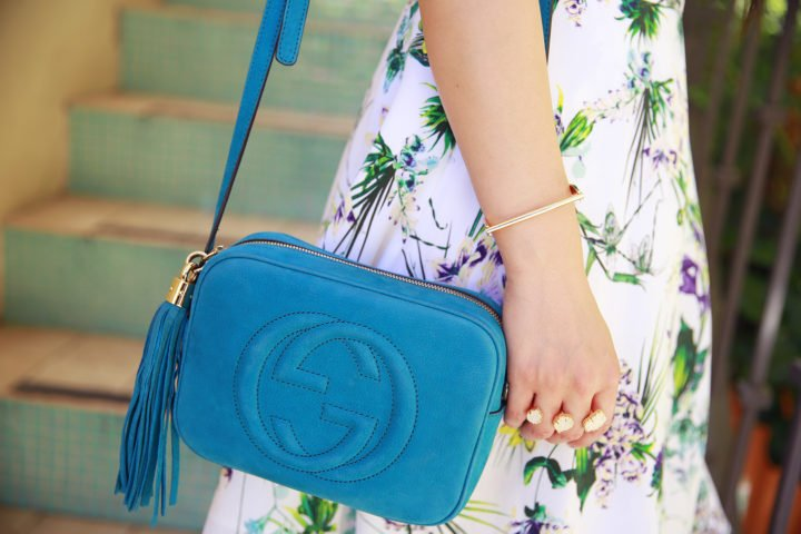 An Dyer wearing Wanderlust Co D Bar Bangle, Kendra Scott Ring, Gucci Soho Disco Teal Suede