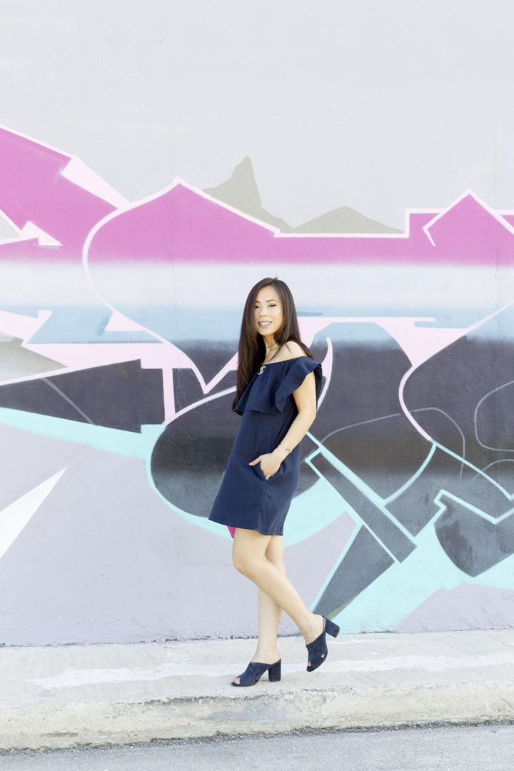 an-dyer-wearing-navy-off-shoulder-dress-suede-mules-in-fat-art-district-fort-lauderdale-street-style-pink-mural