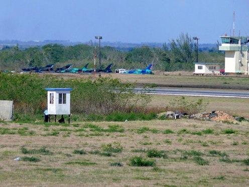 """Pista de aviación en Cuba, marzo de 2009. Tres aeronaves L-39 Albatros (primeros a la derecha) y... dos Mig-21. El primero a la izquierda un Mig-21U y el segundo un Mig-21bis. Cuatro años más tarde el gobierno de La Habana se refiere a los Mig-21 –que aún tiene en explotación- como """"material de guerra obsoleto del siglo pasado""""."""
