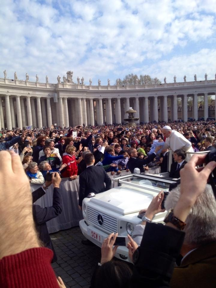 Pope Francis stopping before the Papal Audience to kiss some babies.