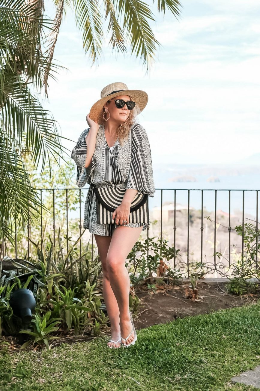 My travel style and one of the outfits I wore in Costa Rica. This black and white romper is perfect for spring and summer and great for your next tropical vacation! Click on the photo to check out the post and get my outfit details! #vacationstyle #summerstyle #romper #costarica #travelstyle #strawhat